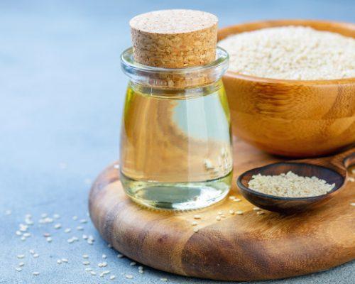 sesame-oil-sesame-seeds-wooden-spoon_202873-49